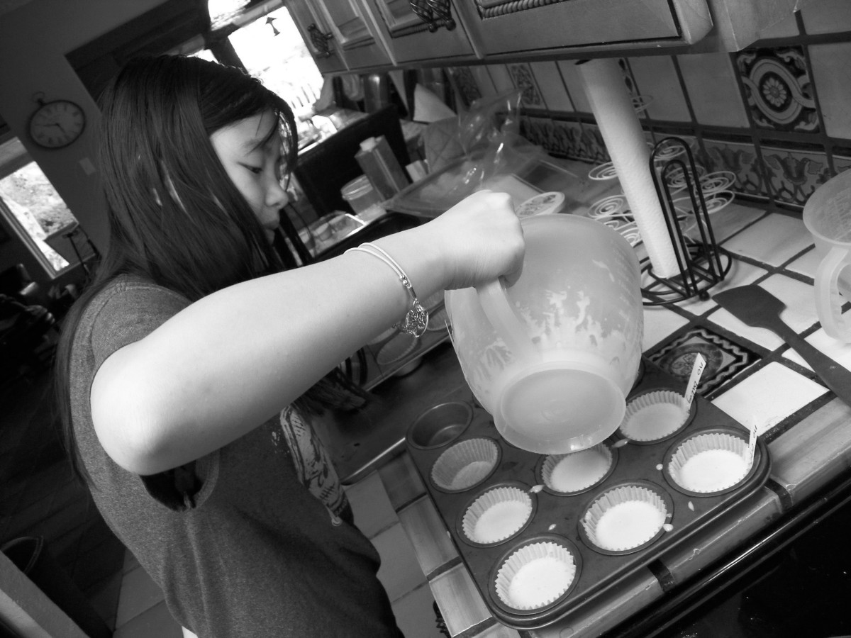 Pouring cupcake batter in pans.