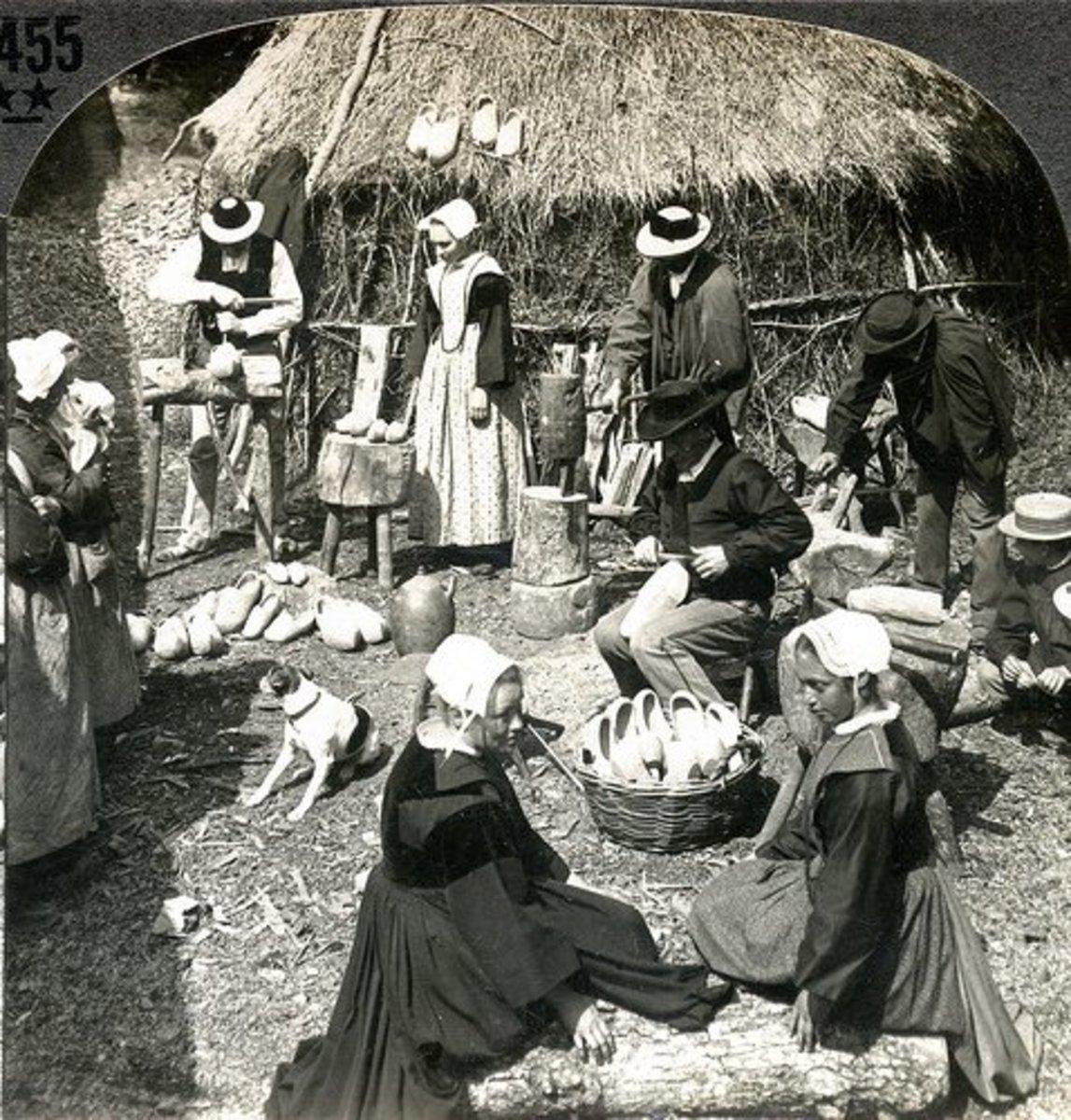 Breton peasants making sabots or wooden shoes.