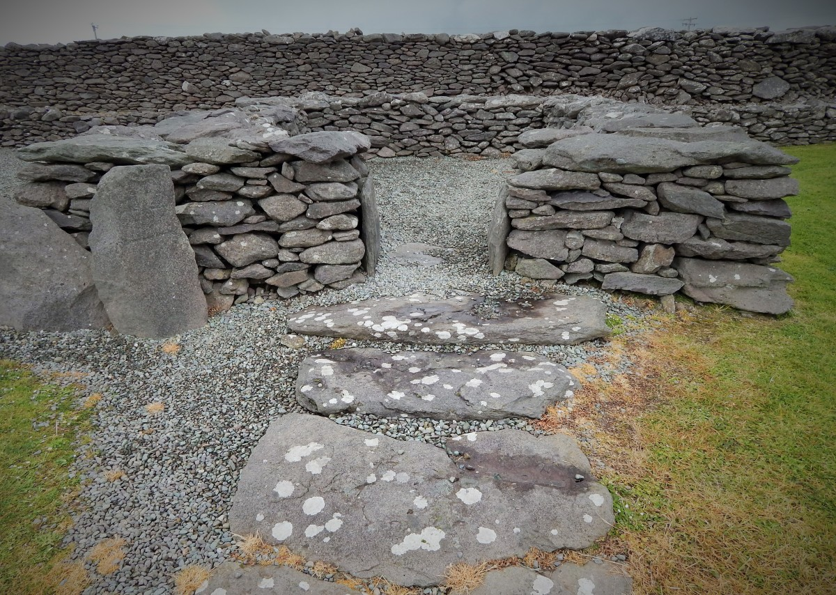 "Remains of a clochán (""beehive"" hut) with decorated stone pillar to left of entrance, Riasc"
