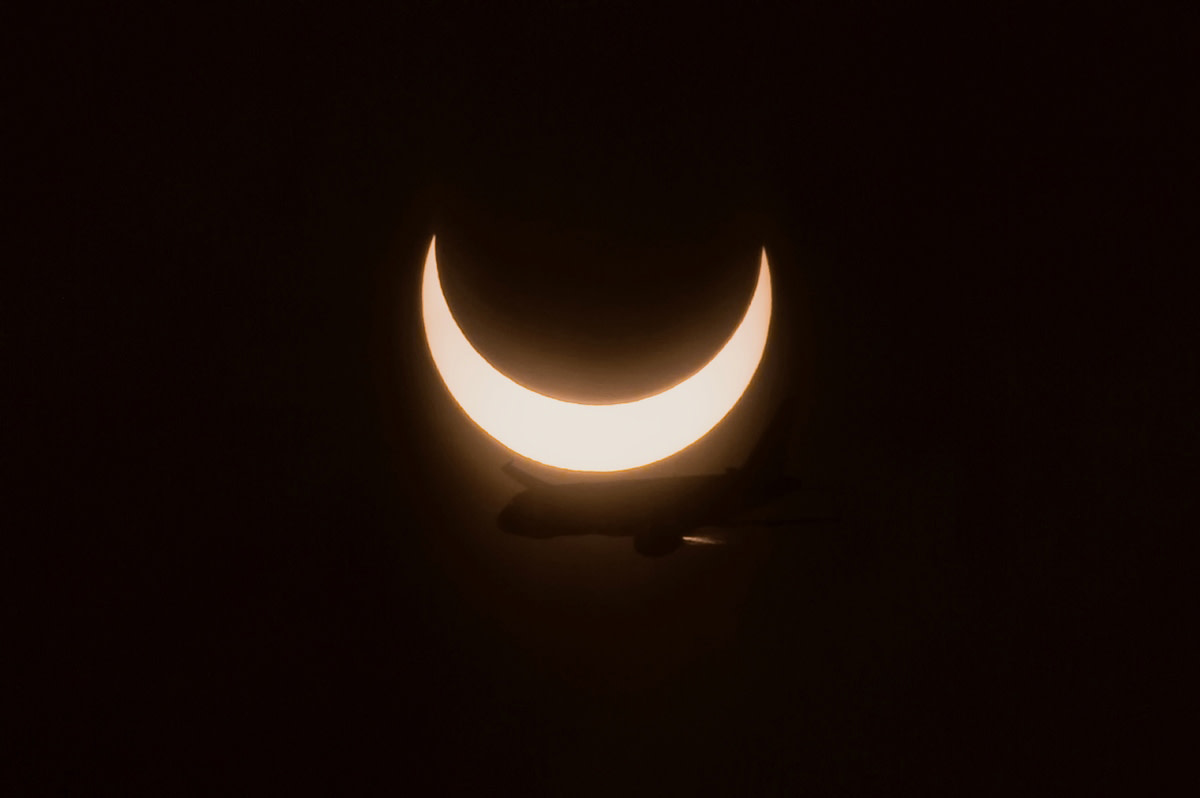 Moon moving in front of Sun during solar eclipse.