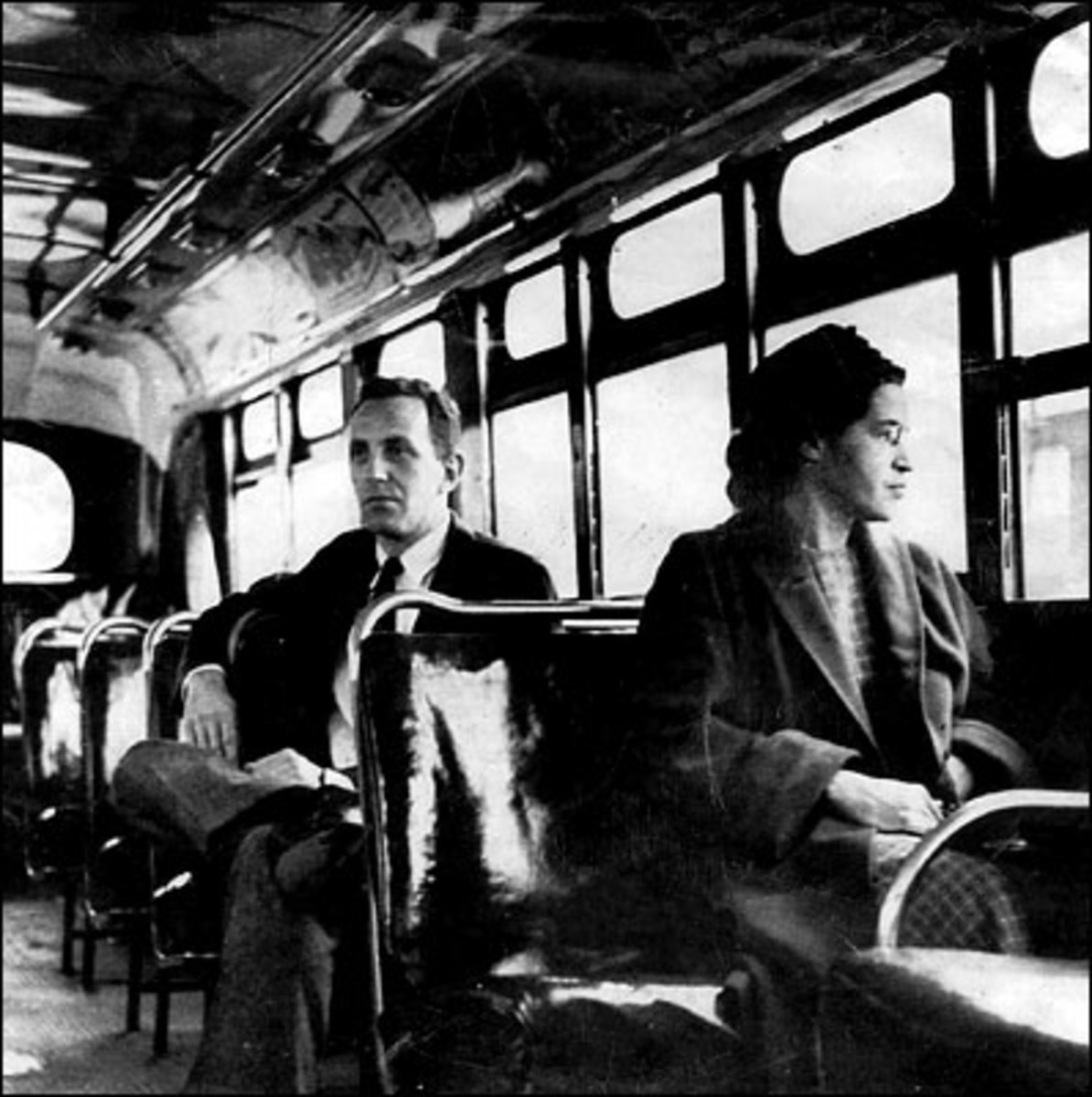 Rosa Parks traveling on a Montgomery bus on the day that the transport system was officially integrated.  Parks became an icon of the civil rights movement but also suffered hardships.  She lost her job in Montgomery and received many death threats.