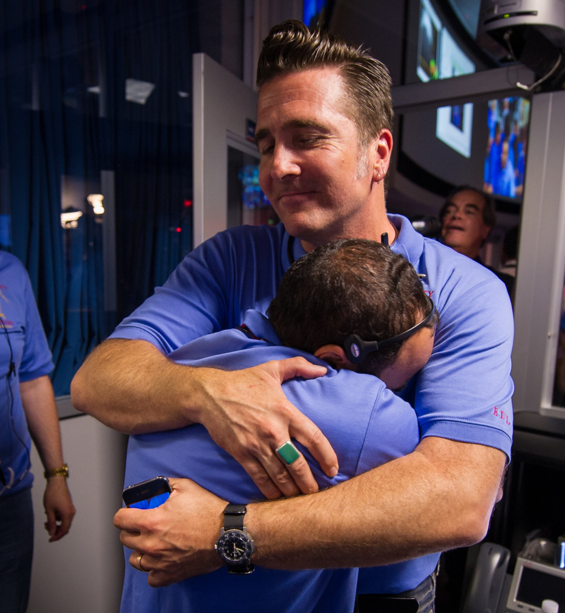 NASA employee Adam Steltzner shares a hug with a hard-working co-worker as the first images from the Curiosity rover roll in.  They worked years for this success.