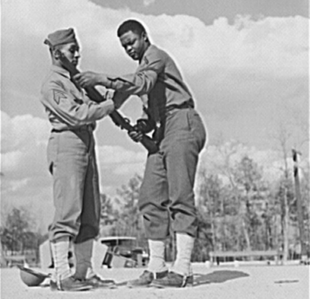 Sgt Williams showing a soldier how to handle his rifle