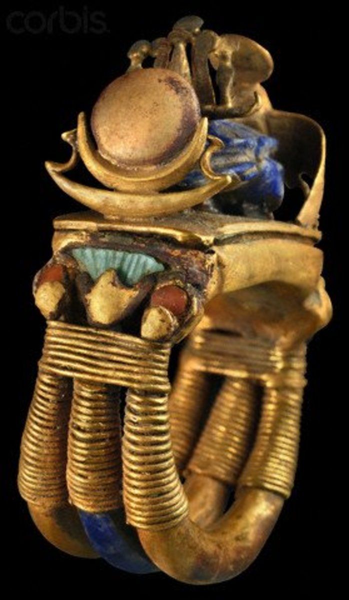 Ring from tomb of Tutankhamun; a shank composed of three bands, the central one set with lapis lazuli, all three are wrapped with gold wire below a motif of three flowers: