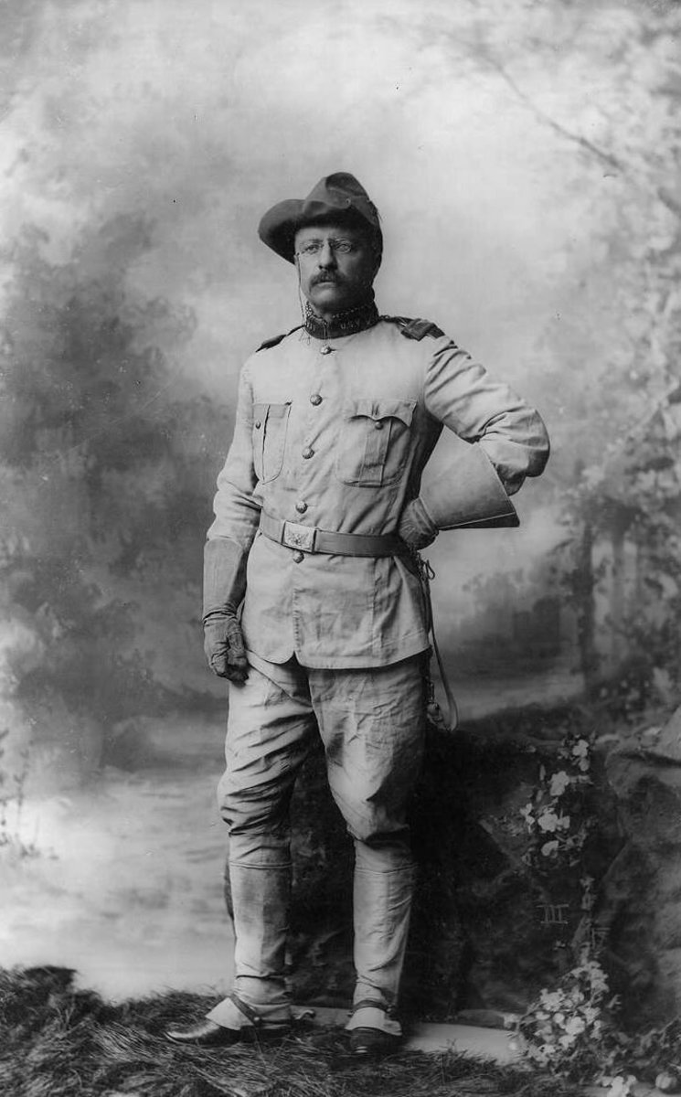 Colonel Theodore Roosevelt, in rough rider uniform, full-length portrait, standing and facing slightly left.