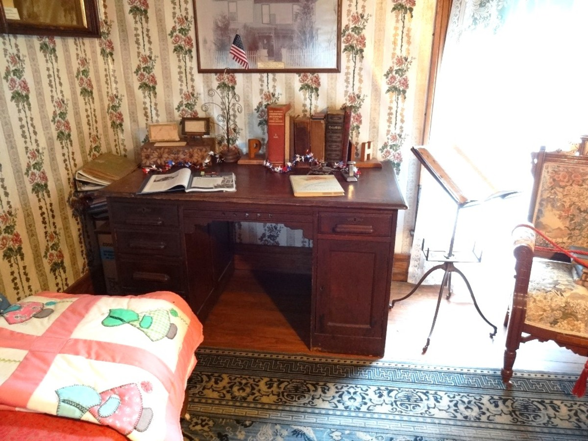 The writing desk in the sitting room, next to a music stand and assorted quilts.