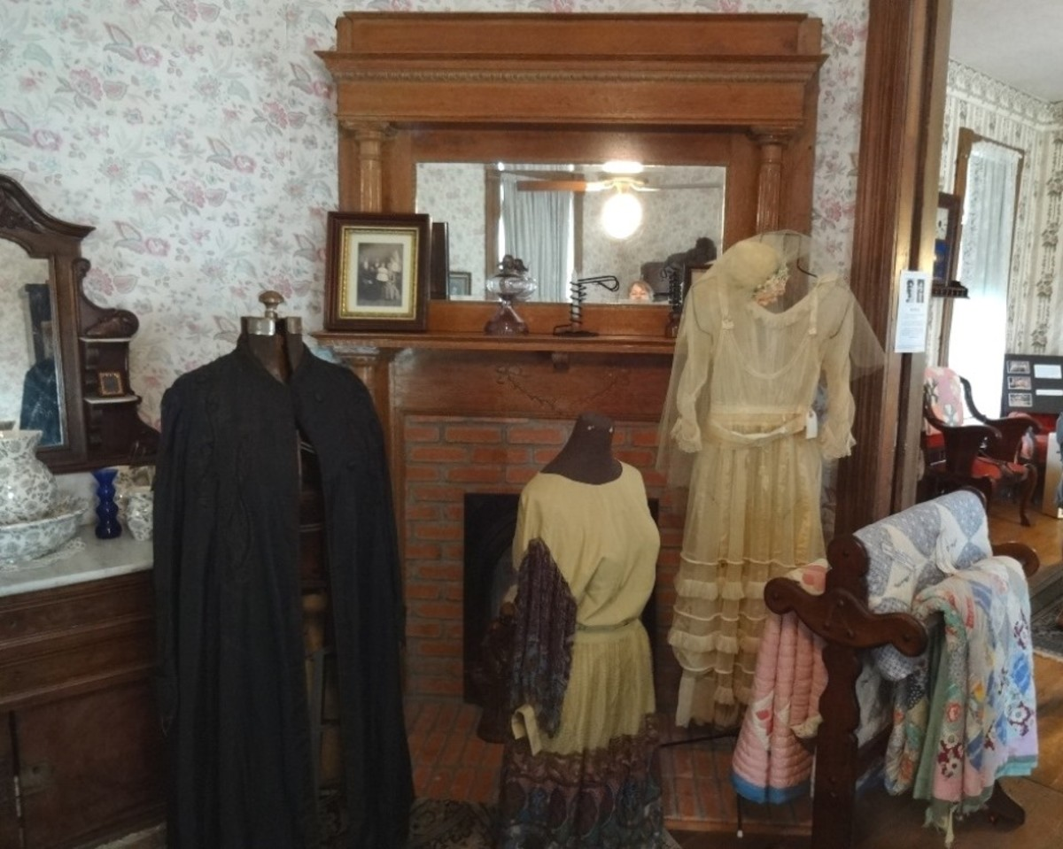 The fireplace shown is on the backside shared wall of the front parlor. On display are costumes worn during the era.