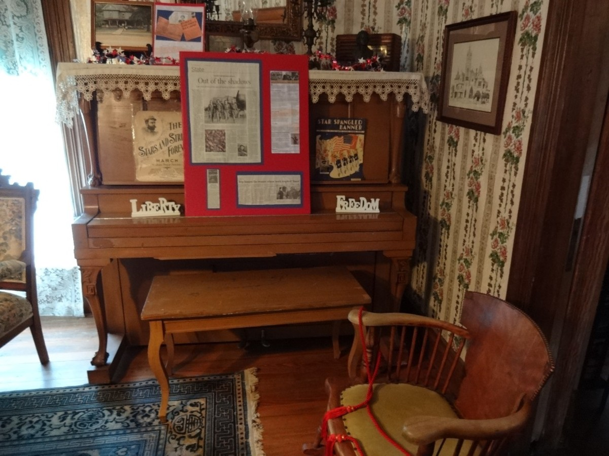 The main parlor held a piano, rosewood chairs, a wool tapestry rug and antique photos.