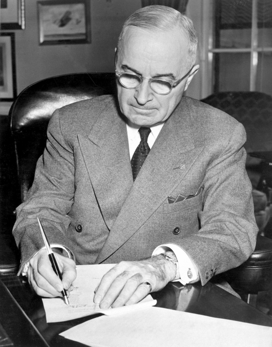 President Harry S. Truman is shown at his desk at the White House signing a proclamation declaring a national emergency.