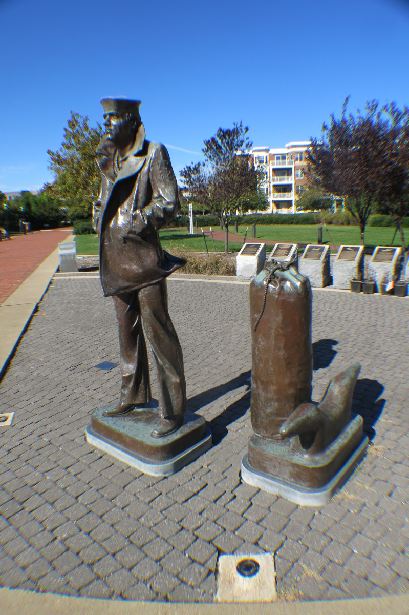 Statute of Lone Sailor in Jacket with collar up and Duffel Bag at his side ready to go to Sea