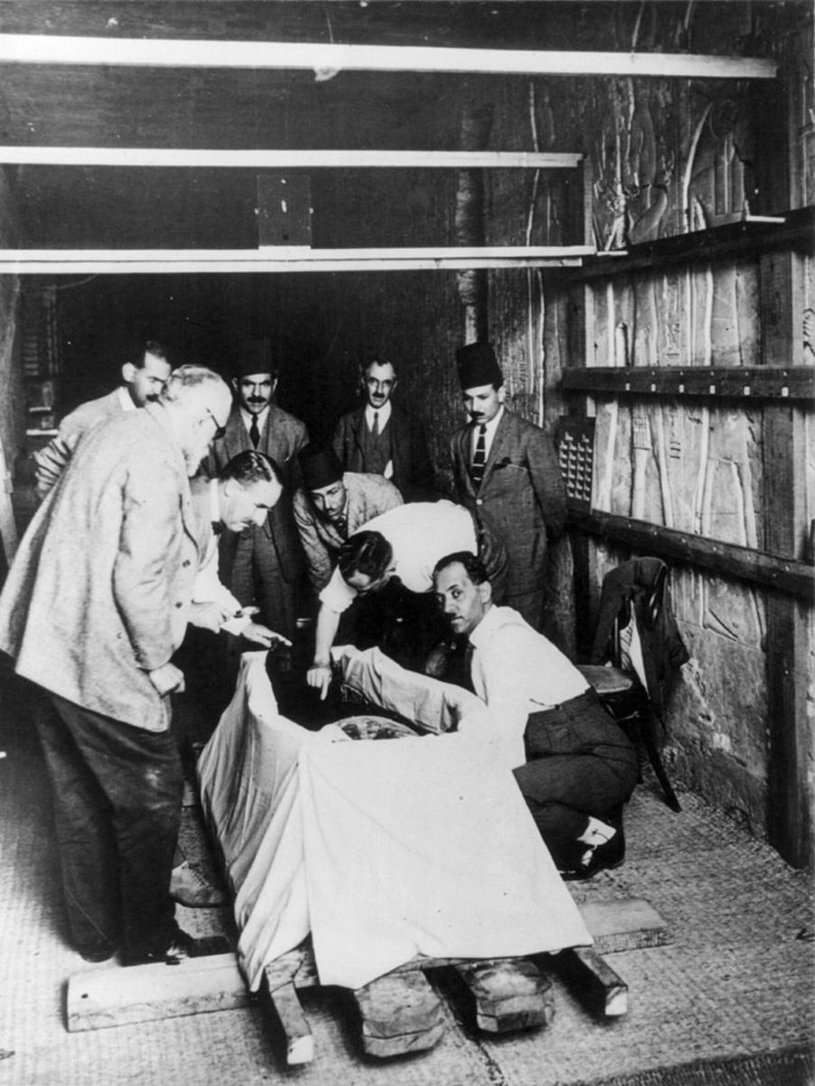 Howard Carter, with magnifying glass, leaning over Tutankhamun during the unwrapping of his mummy in 1925.