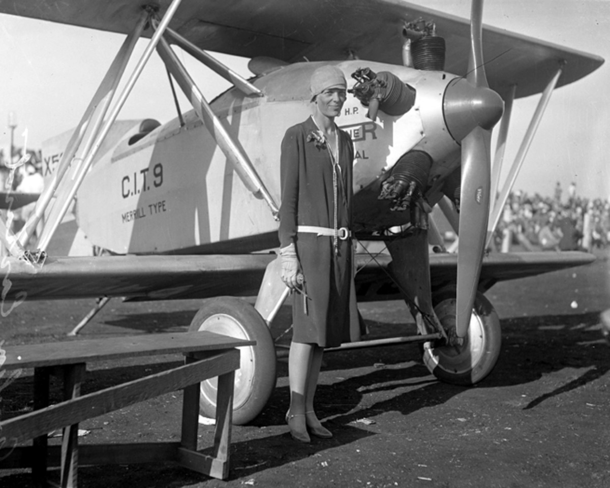 Amelia Earhart poses by her biplane in 1928