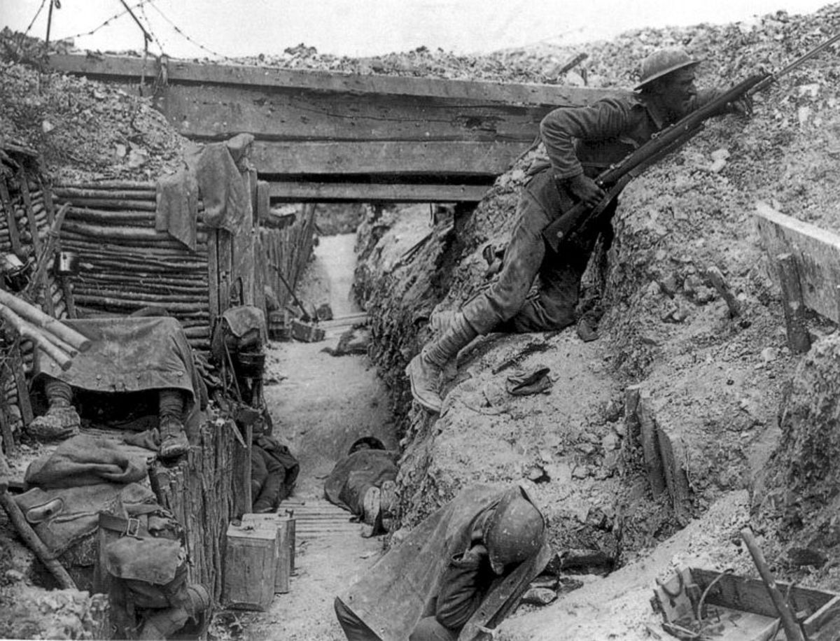British troops occupying a German trench on the Somme. One soldier is on lookout duty while the others rest.