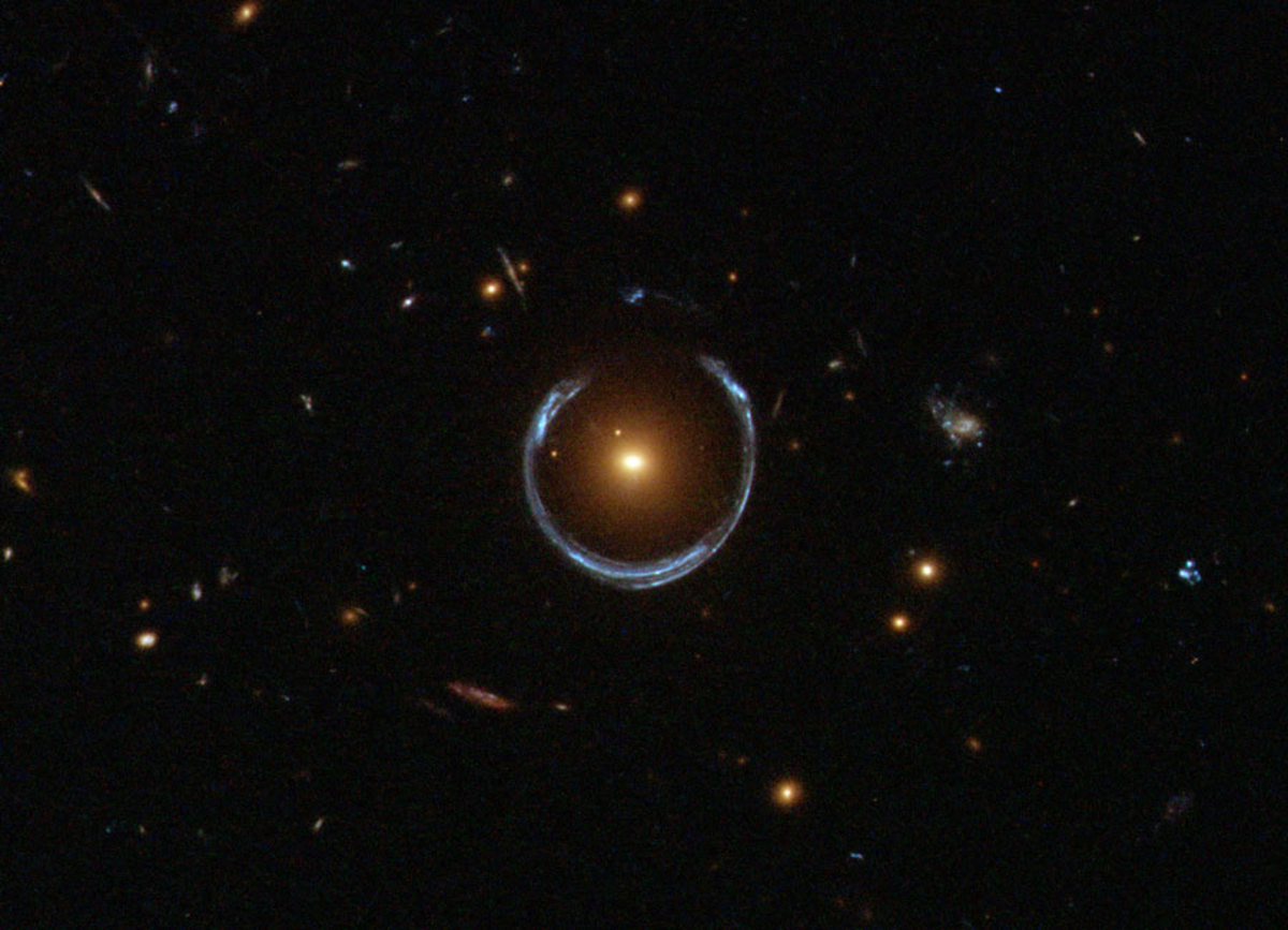 An image from the Hubble Space Telescope showing the characteristic 'Einstein ring' pattern produced by gravitational lensing. The red galaxy acts as a lens for light from a distant blue galaxy. A distant exoplanet would produce a similar effect.