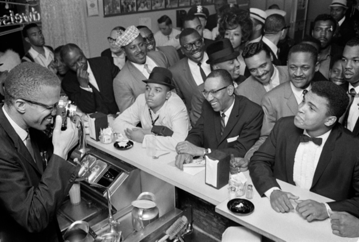 Malcolm X photographing Cassius Clay after Clay became the world heavyweight champion (1964). Clay would become one of the most famous converts to the Nation of Islam, changing his name to Muhammad Ali.