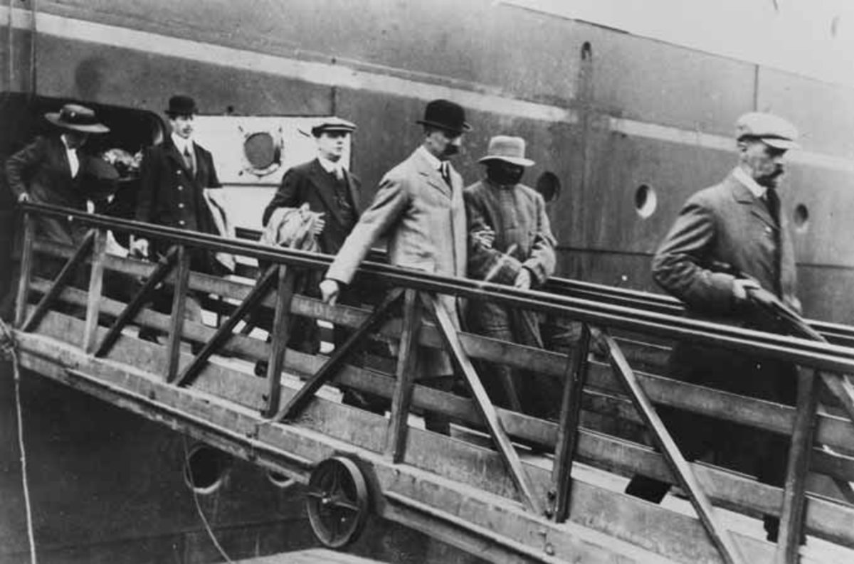 Inspector Dew in bowler hat and light overcoat escorts Crippen off the Montrose.