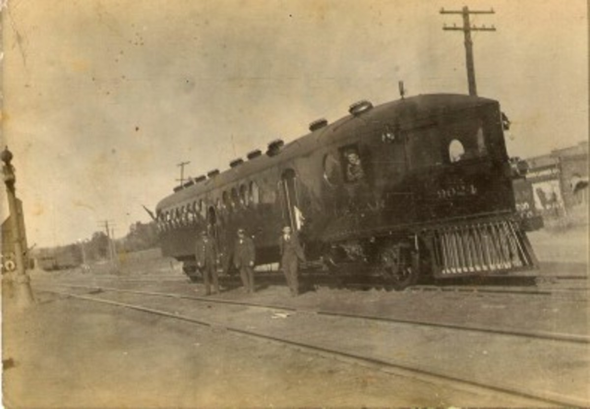 Railroad men in their uniform standing by an unusual passenger railroad car, Heavener