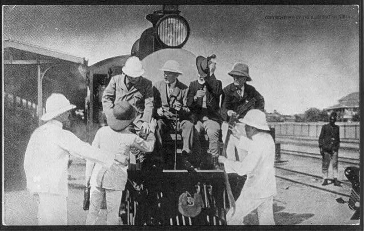 Theodore Roosevelt (left on the buffer beam) poses with the pith-helmeted colonial administrators on the Uganda Railway.