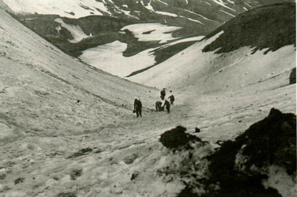 U.S. soldiers carrying supplies on Attu Island showing the inhospitable terrain.
