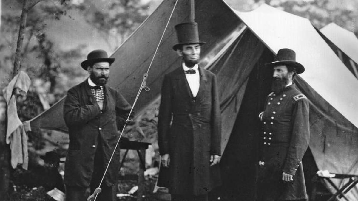 Abraham Lincoln standing outside a military tent with Allan Pinkerton and General McClernan