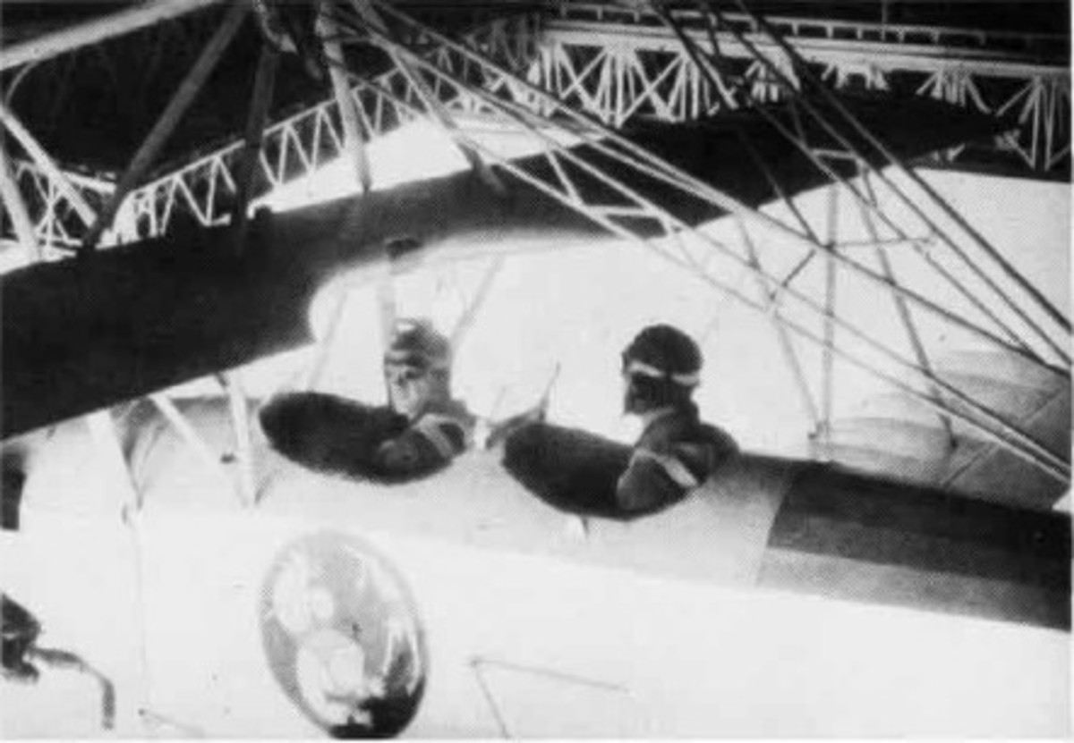 Aircrew in their airplane that is attached to the airship USS Macon.