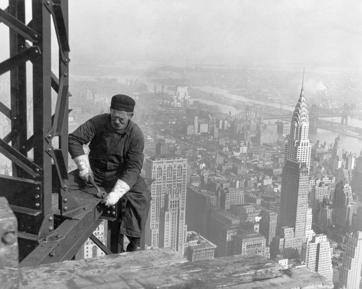 A worker sat on the edge of the Empire State Building with the completed Chrysler Building in the background