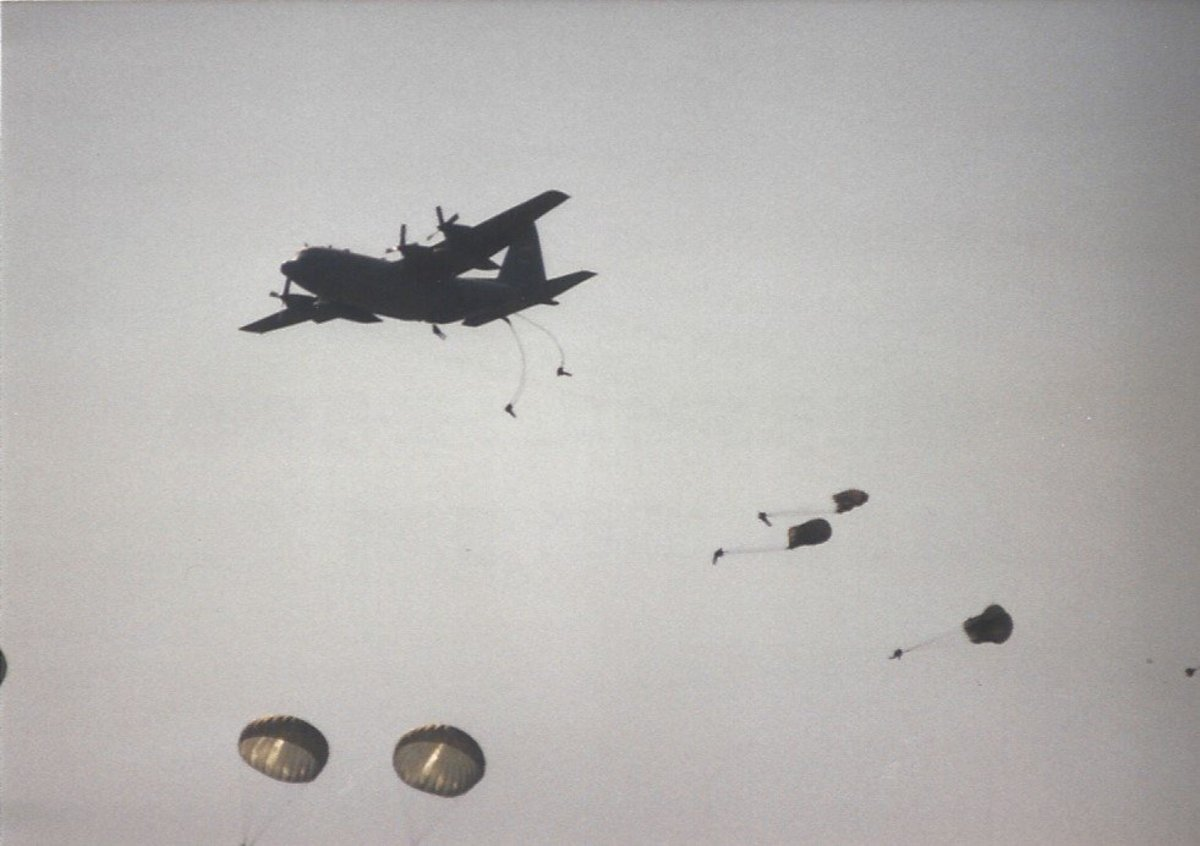 Paratroopers jumping from a C-130 during a mass parachute drop.