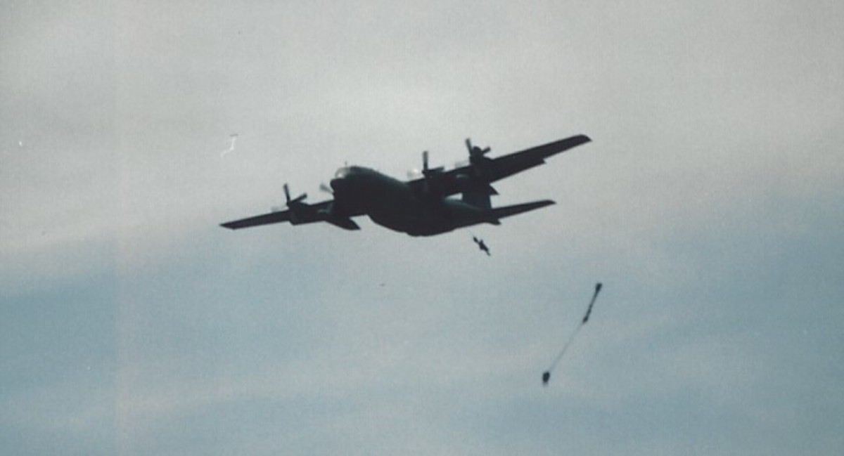 Paratroopers jumping out of a C-130 during a mass parachute jump at Andrews, AFB, MD.