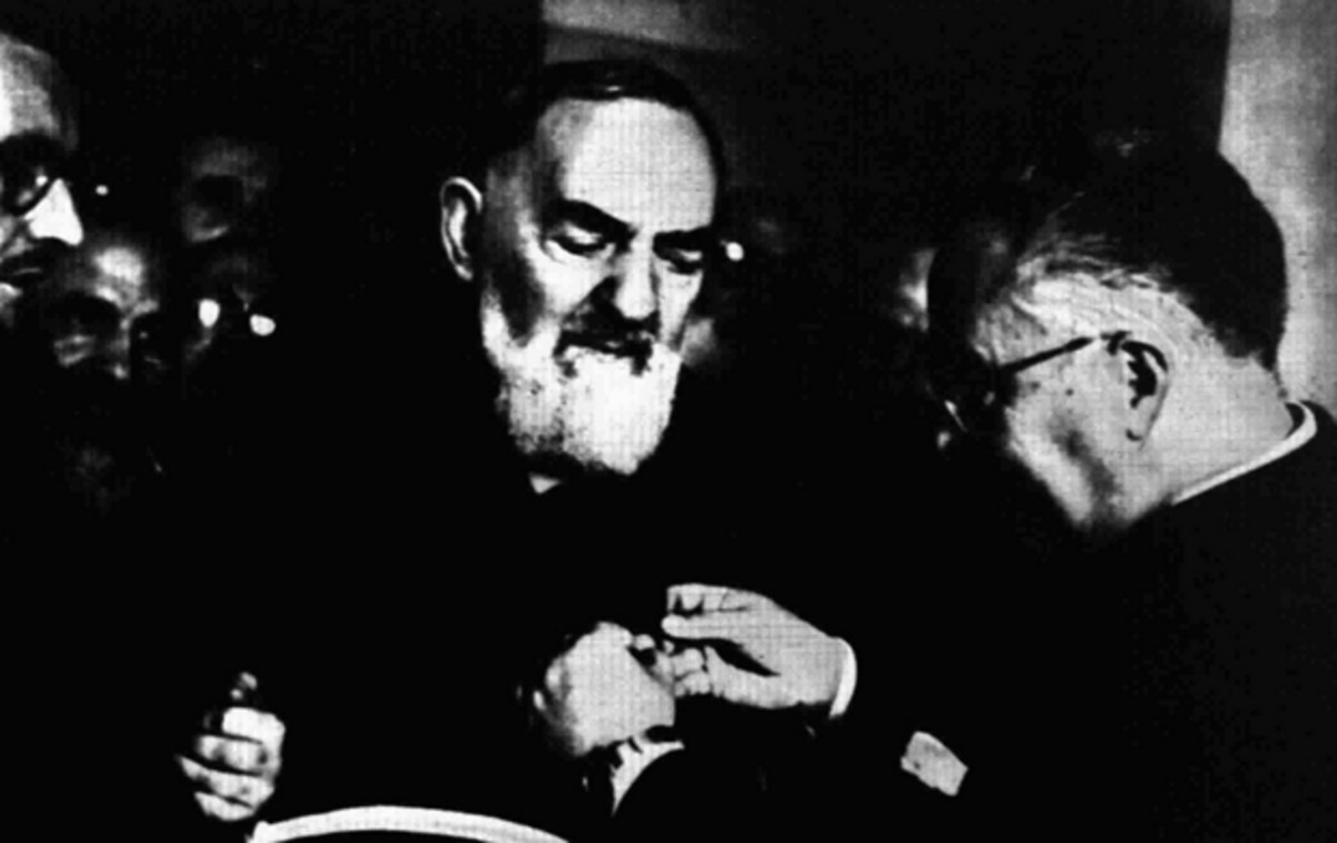 Padre Pio receives a medal for his humanitarian efforts.