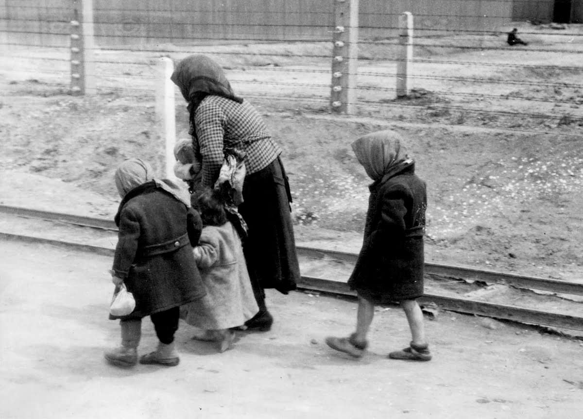 Hunched over and beaten down, a woman and her children in Auschwitz, perhaps on their way to the gas chambers.