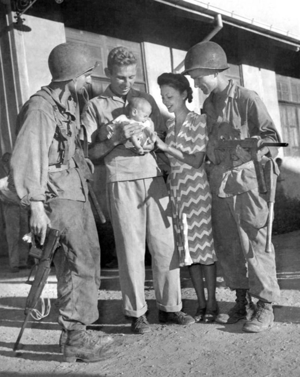 Two former internees and their baby daughter with paratroopers who saved them.