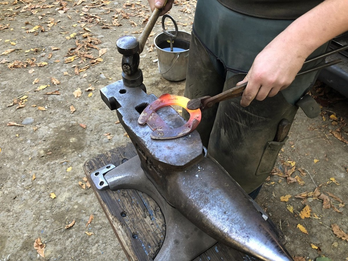 This horseshoe is made of iron. The farrier makes it really hot in a forge so that it gets soft like toffee and can be hammered and bent to the shape he wants.