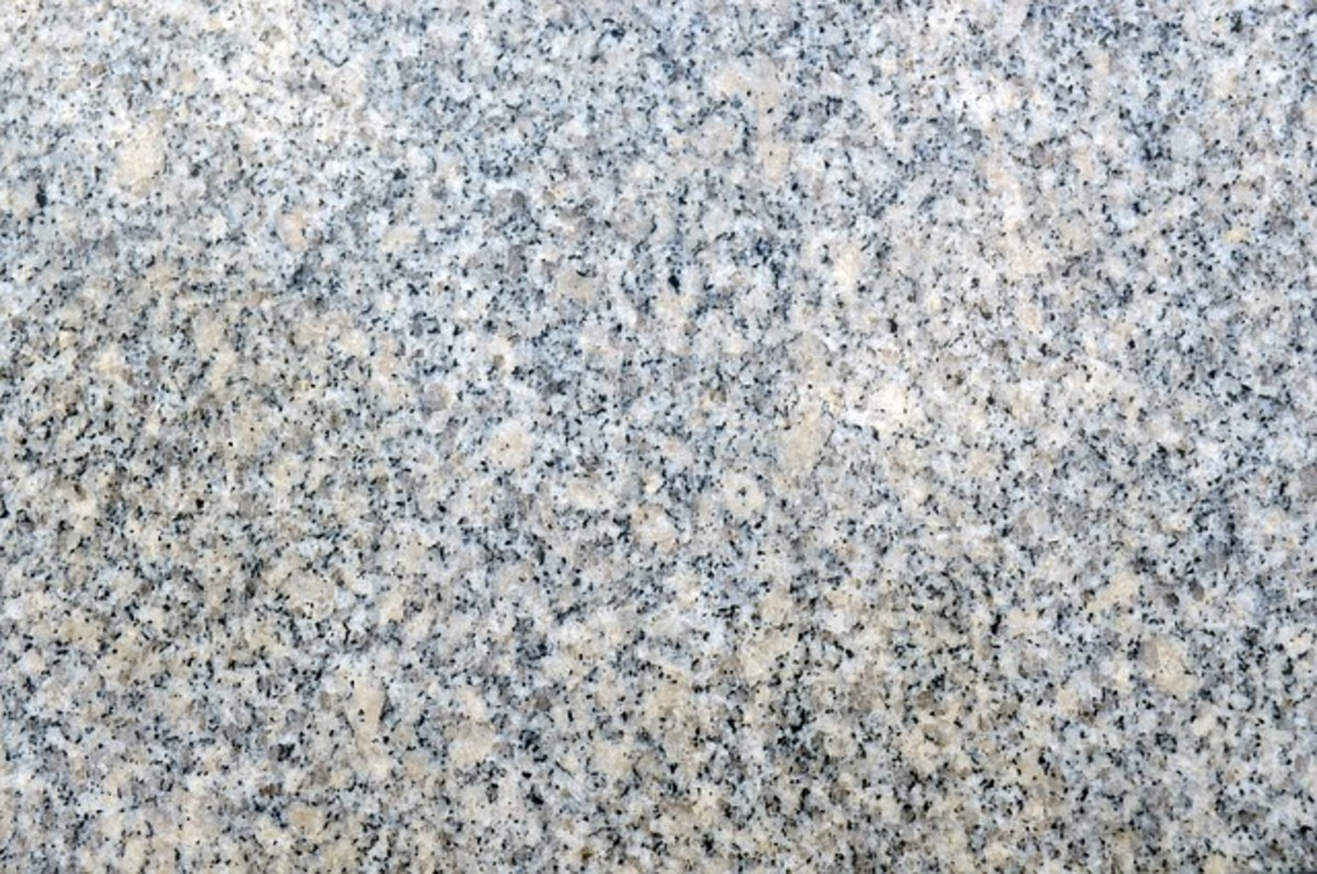 A photograph showing the mineral composition of a slab of granite. The white areas are quartz, the buff-colored parts are feldspar, and the black specs are mica.