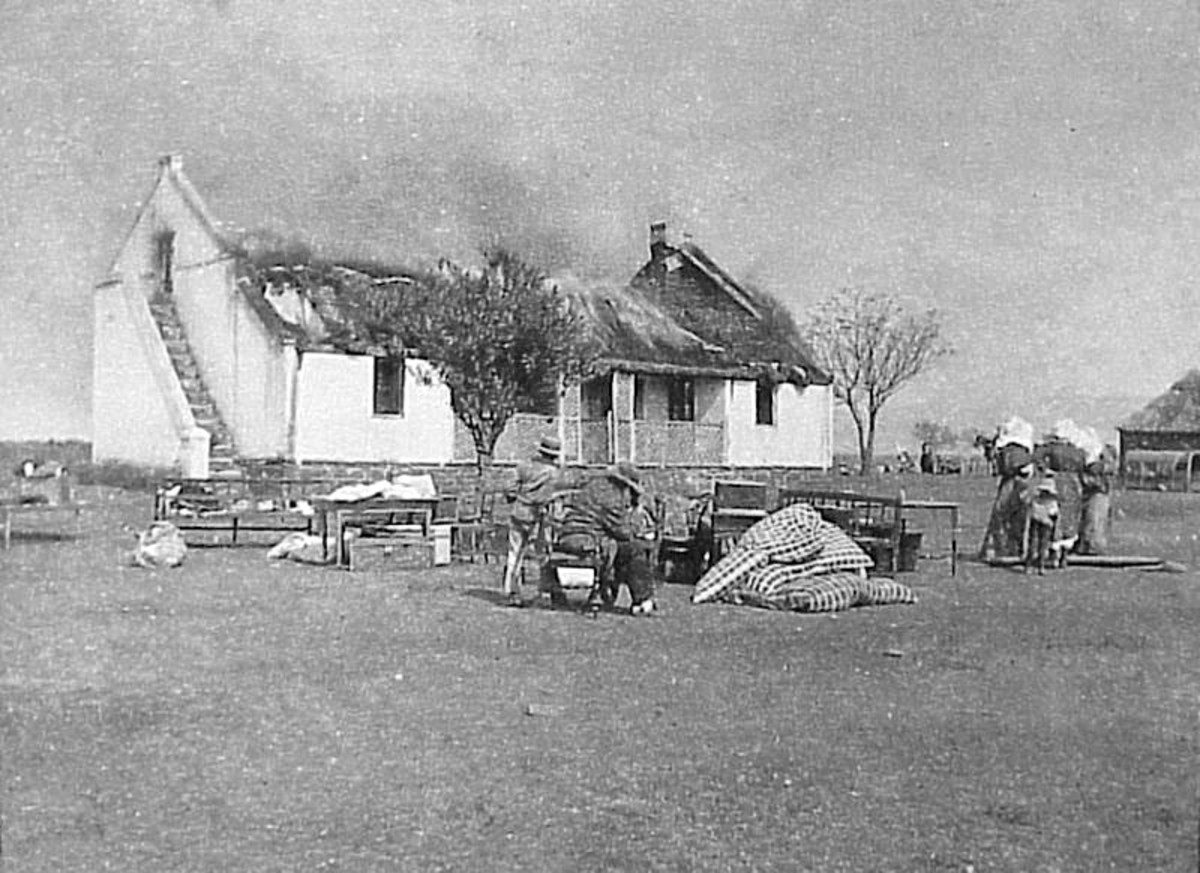 One British response to the guerrilla war was a 'scorched earth' policy to deny the guerrillas supplies and refuge. In this image Boer civilians watch their house as it is burned.