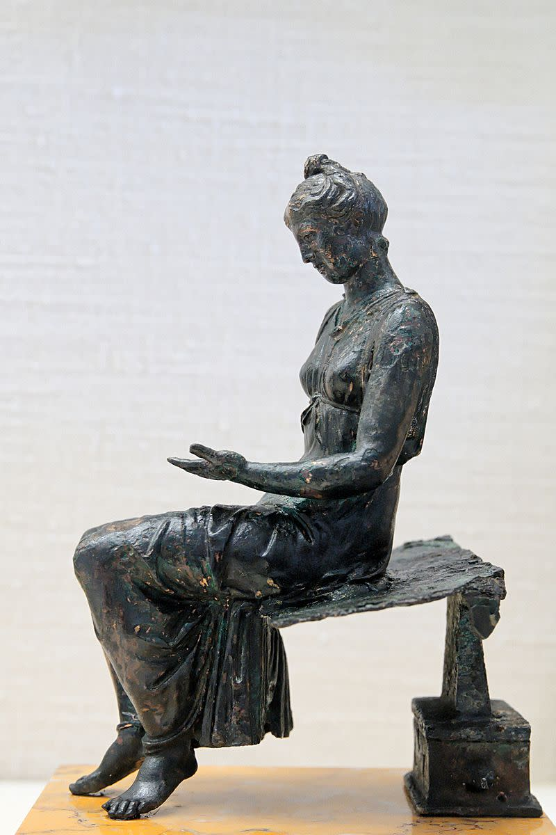 Statuette of girl reading in ancient Rome. Notice the artist's attention to detail in this statue.