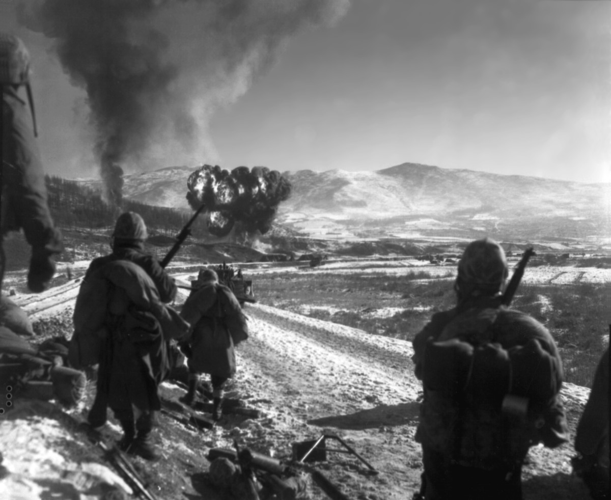 Marines watch F4U Corsairs drop napalm on Chinese positions in Korea during the withdrawal from the Chosin Reservoir. (1950)