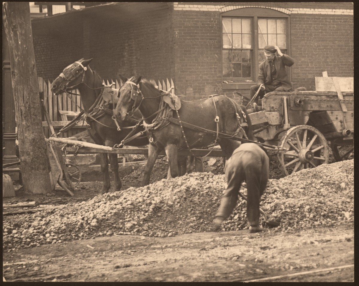 Horse drawn wagon at an unknown street construction site.