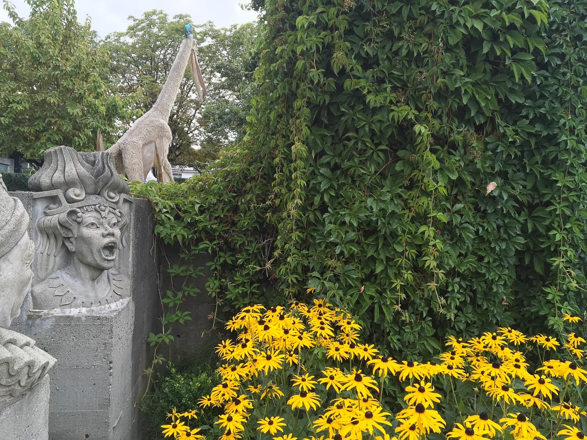 An unusual combination: sculptures of characters from Italian operas, black-eyed Susan flowers, Boston ivy leaves, and a Quetzalcoatlus model in the background
