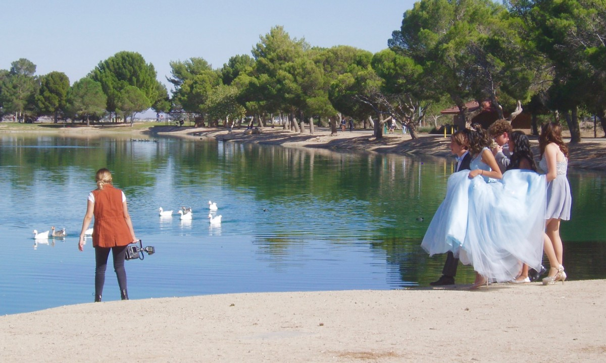 This photograph is of Apollo Park—a reclamation pond in Lancaster CA. Here you see preparations to photograph a quinceanera party. This photo could be used to emphasize the pros of designing a reclamation pond to also act as a public park.