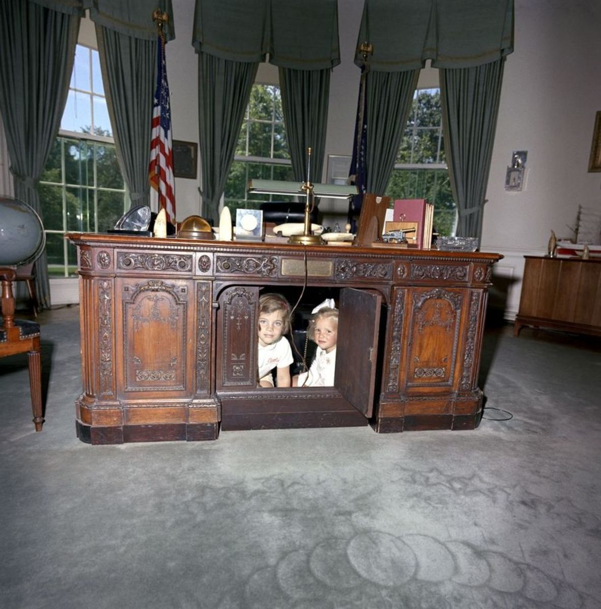 Kennedy children peek out through the kneehole door.