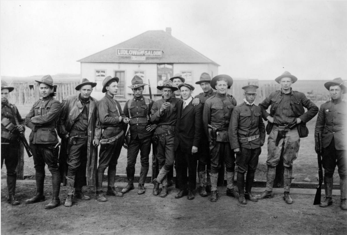 Members of the Colorado National Guard, called in to suppress the UMWA strike against CF&I, pose outdoors with a civilian near the Ludlow Home Saloon in Ludlow, Las Animas County, Colorado. They wear ammunition belts with holsters.