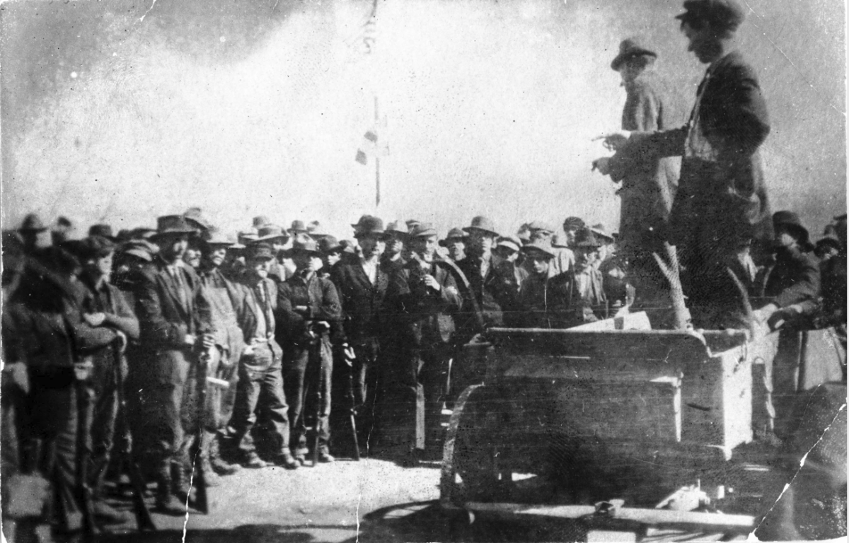 UMWA labor union organizers address coal miners on strike against CF&I, in Ludlow, Las Animas County, Colorado; United States flags are over the crowd.