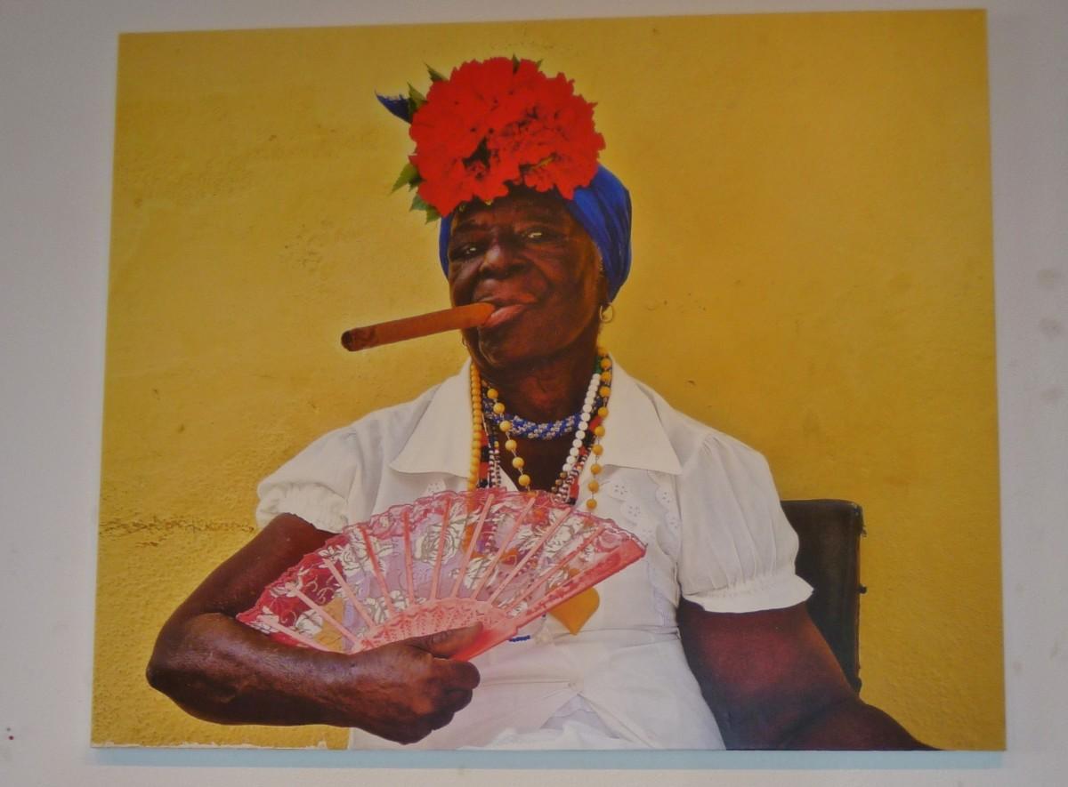 Woman smoking a cigar in Cuba Behind Open Doors by Kevin Douglas West
