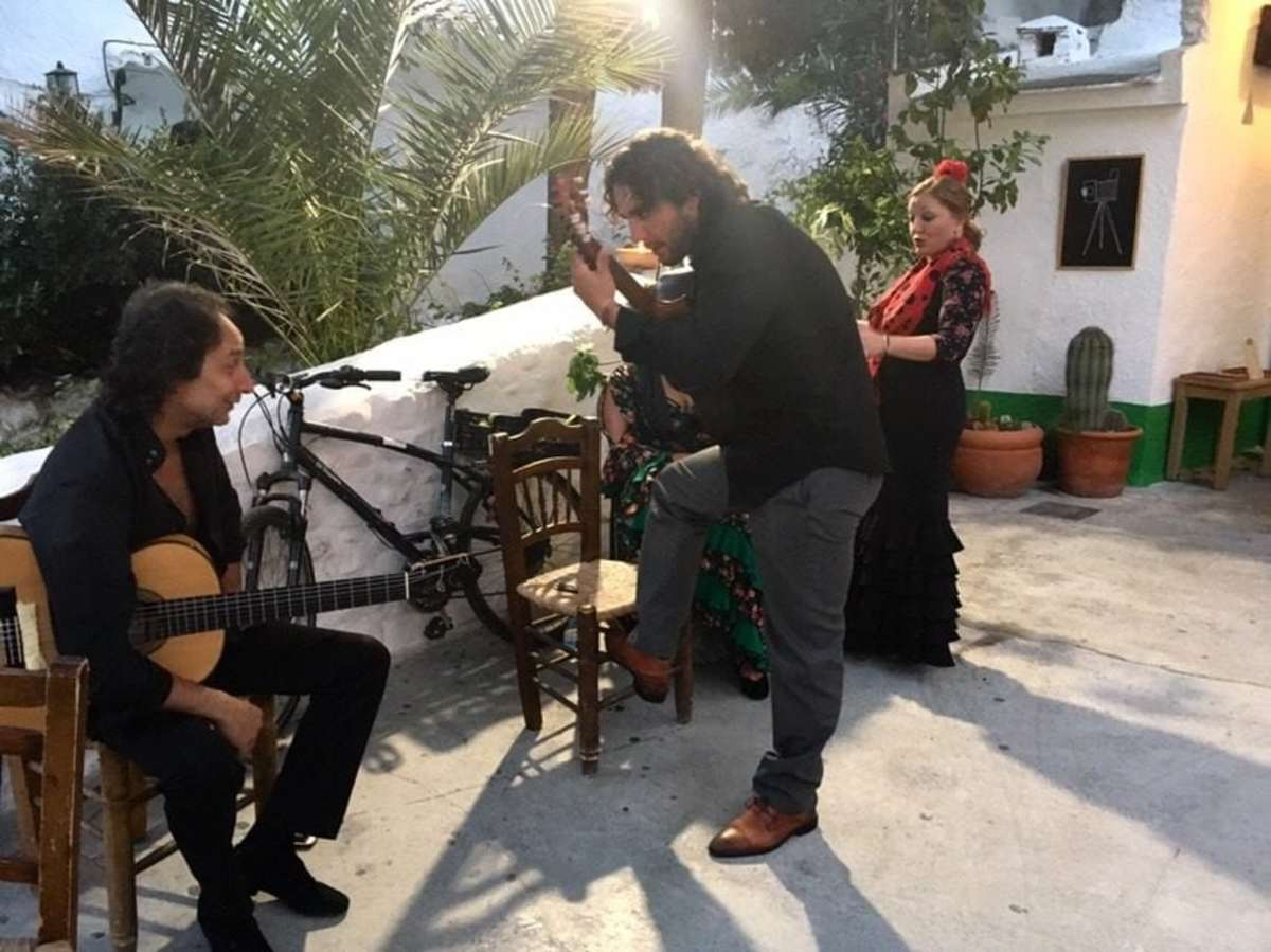 Flamenco guitarists and a dancer outside a traditional cave-house in Granada.