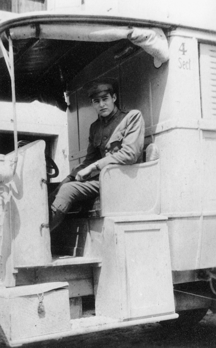 WW1: 19-year-old Ernest Hemingway in an American Red Cross Ambulance in Italy, 1918, reportedly taken near Caporetto. Despite being severely wounded, Hemingway continued helping Italian wounded, for which he received an Italian medal for bravery.