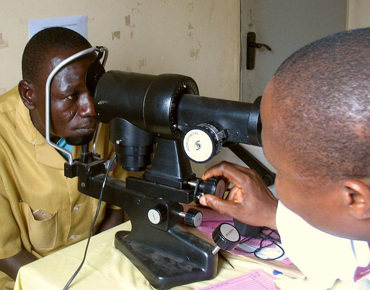 A patient being tested with a keratometer.