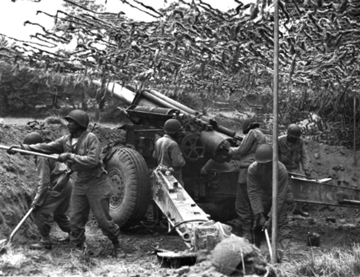 A gun section of the 333rd Field Artillery  preparing for action in Normandy.