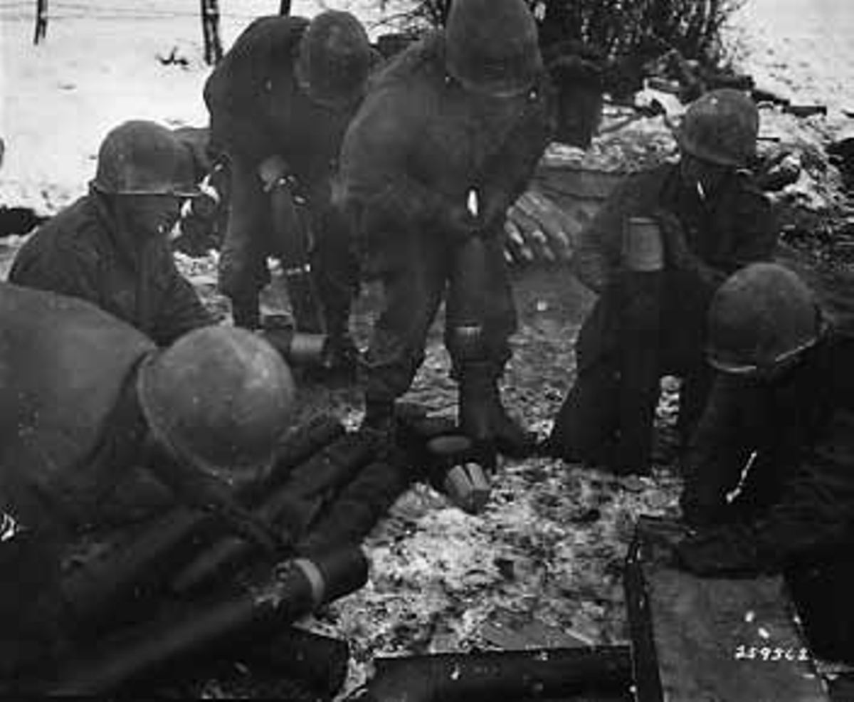105mm ammo crew arming shells during the Battle of the Bulge (591st FAB -106th ID). Love the cigarettes around all that powder.