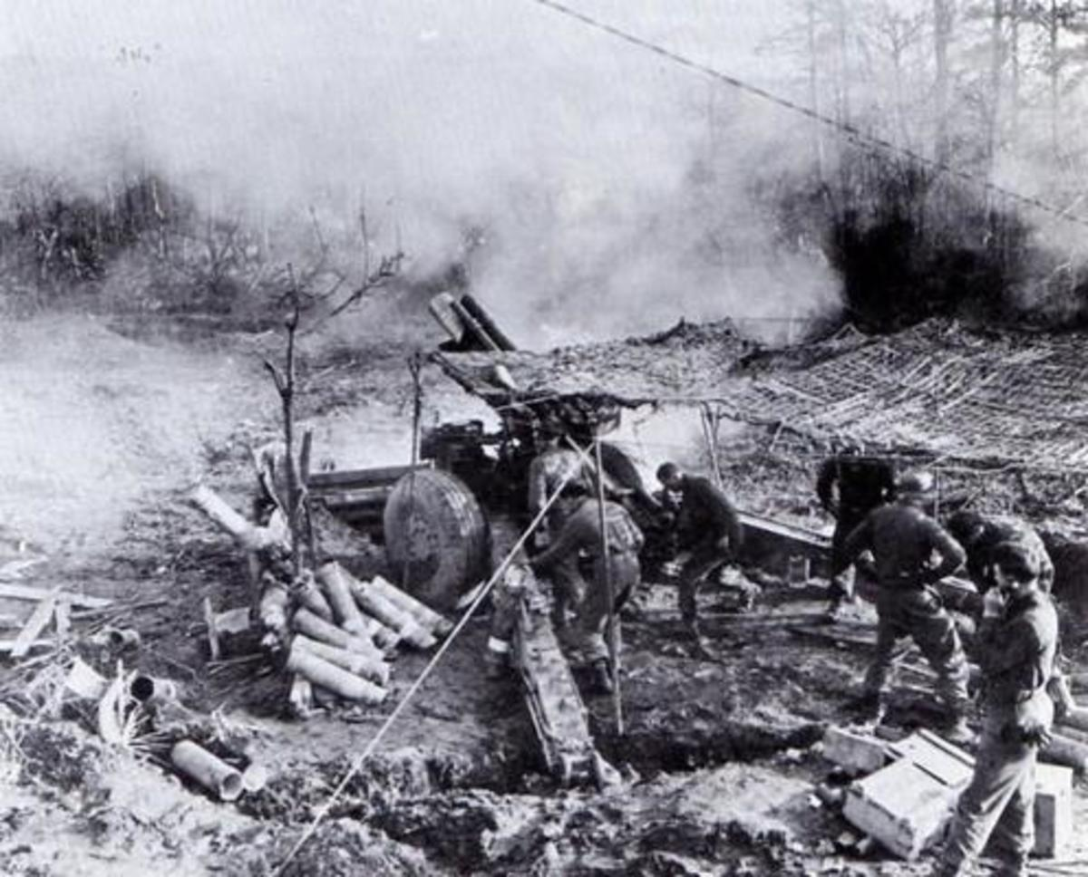 155mm gun section, Huertgen Forest 1944. Great example of crew members in action. The corporal gunner to the left of the breech and #1 gunner to the right. One of the loaders disposing of the casing.  3 ammo crew to the right. Section Sgt is on phone
