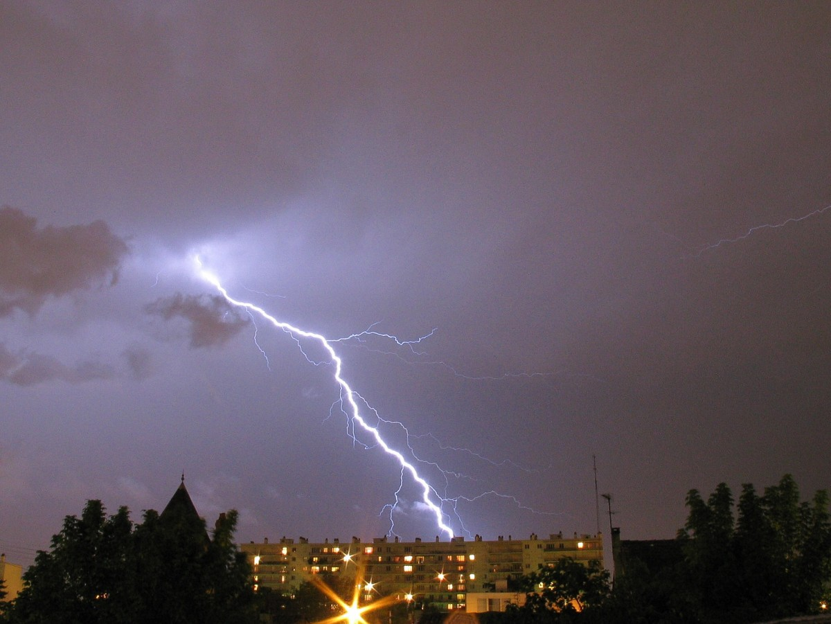 Lightning is sometimes dangerous. This photo shows a lightning strike near buildings.